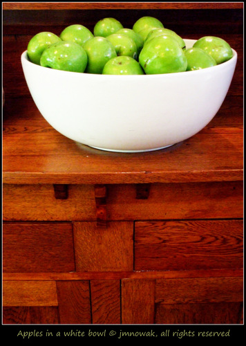 Green apples in a white bowl.